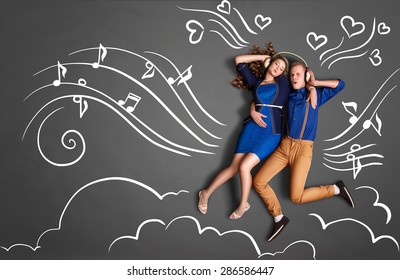 Happy valentines love story concept of a romantic couple sharing headphones and listening to the music against chalk drawings background of notes, player icons and clouds.