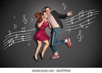 Happy valentines love story concept of a romantic couple sharing headphones and listening to the music against chalk drawings background.