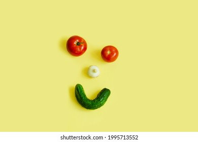 Happy vegetables, vegetable face, tomato eyes, garlic nose, cucumber smile, top view, on a yellow background, copy space.