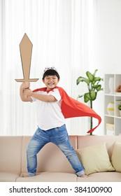 Happy Vietnamese boy with big cardboard sword pretending to be a knight