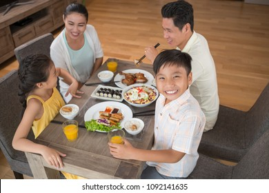 Happy Vietnamese boy dining with family at home, view from above