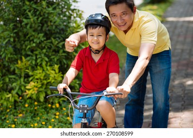 Happy Vietnamese boy learning to ride a bike with help of his father