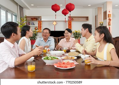 Happy Vietnamese family celebrating Tet at home; couplets with best wishes for the upcoming year in the background