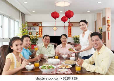 Happy Vietnamese family having dinner for Tet celebration; couplets with best wishes for coming year in the background