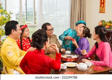 Happy Vietnamese family at the table celebrating Tet
