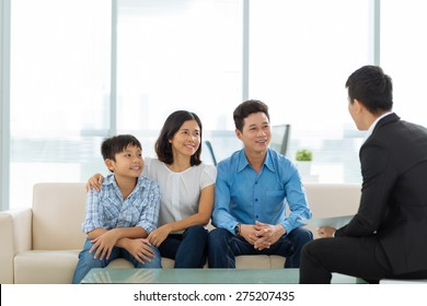Happy Vietnamese family of three at the meeting with real estate broker
