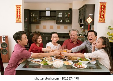 Happy Vietnamese family toasting with glasses of juice. Scrolls wishing luck and wealth in the background
