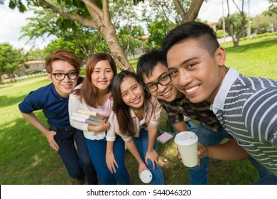 Happy Vietnamese young man taking selfie with his classmates
