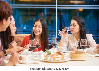 Happy Vietnamese young people eating and talking at dinner table