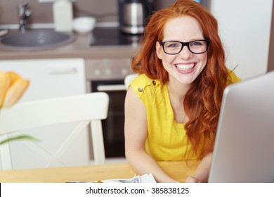 Happy vivacious young redhead woman wearing glasses sitting at the table at home with a computer grinning candidly at the camera