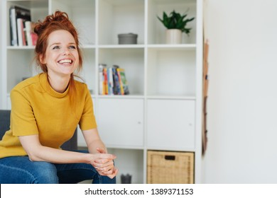Happy vivacious young woman with her long red hair tied up relaxing at home in denims on a sofa looking up with a joyful smile
