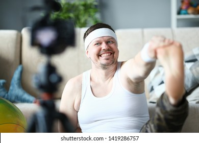 Happy Vlogger Record Stretching Exercise on Camera. Bearded Man Shooting Aerobic Warmup for Leg on Digital Camcorder for Sport Vlog. Male Doing Gymnastics in Apartment. Healthy Lifestyle Photo
