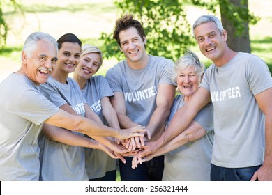 Happy volunteer family putting their hands together on a sunny day