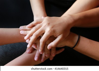 Happy volunteer family putting their hands together - close up of creative team sitting at table and holding hands on top of each,  teamwork hand group unit