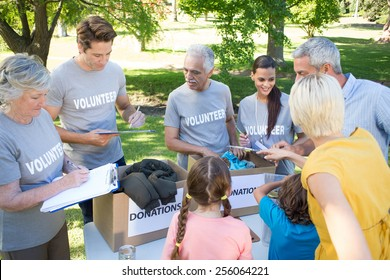 Happy volunteer family separating donations stuffs on a sunny day