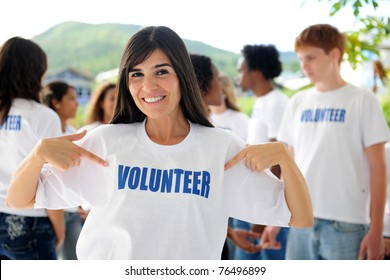 happy volunteer woman showing and group outdoors