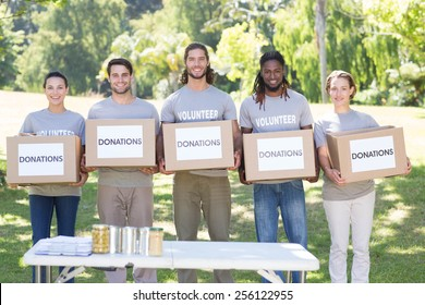 Happy volunteers with donation boxes in park on a sunny day