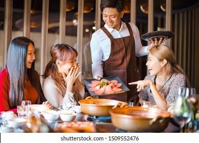 Un serveur ravi apporte des tranches de boeuf et sert un groupe d'amis au restaurant.