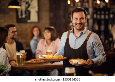 Happy waiter holding plates with food and looking at camera while serving guests in a restaurant.