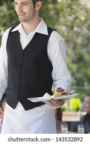 Happy waiter holding slice of pie at outdoor cafe
