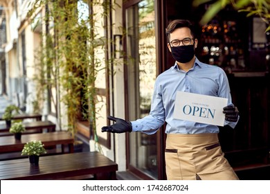 Happy waiter with protective face mask holding open sign while standing at cafe doorway.