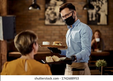 Happy waiter wearing protective face mask and gloves while bringing food to a customer in a pub.