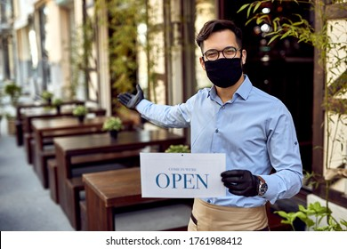 Happy waiter wearing protective face mask and holding open sign while reopening after COVID-19 epidemic.  - Shutterstock ID 1761988412