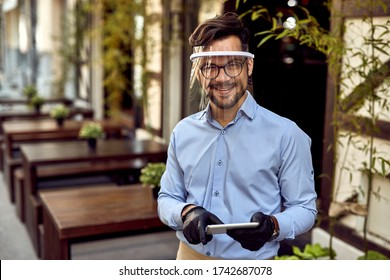 Happy waiter wearing visor while working on touchpad at outdoor cafe and looking at camera.