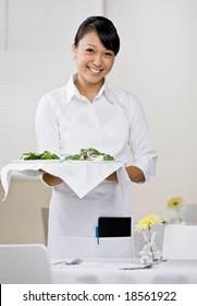 Happy waitress serving healthy salad for lunch in elegant restaurant