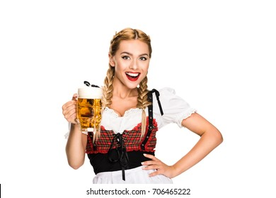 happy waitress in traditional german costume holding beer glass on Oktoberfest, isolated on white