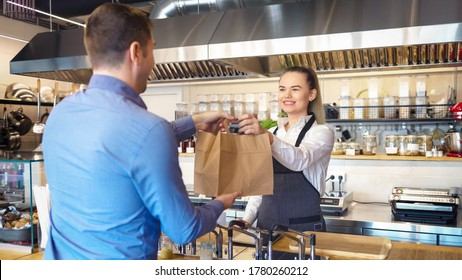 Happy waitress wearing apron serving customer at counter in small family eatery restaurant - Small business and entrepreneur concept with woman owner in eatery with takeaway service delivery