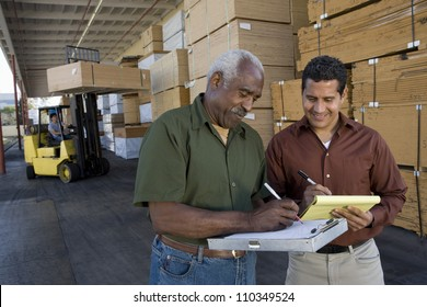 Happy warehouse workers writing on clipboards