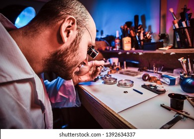 Happy watchmaker  is repairing cutomer's watch at his own workshop.