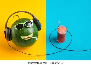 happy watermelon face listening to music and juice in glass , split color background.