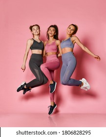 Happy wealthy sporty girls friends in pink, grey, brown training suits stylish sportswear have fun jumping. Fitness and yoga girls posing on pink background