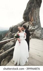 Happy wedding couple, bride and groom posing near rocks with beautiful views