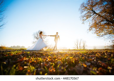 Happy wedding couple charming brunette bride and groom dancing in the park