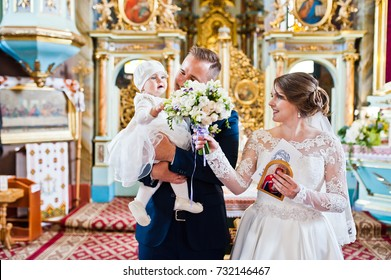 Happy wedding couple in the church with their little baby daughter on their wedding day.
