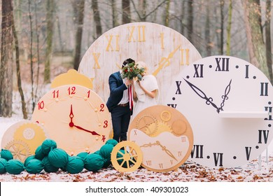 Happy wedding couple kissing at the big vintage clocks in  autumn forest. Creative decorations