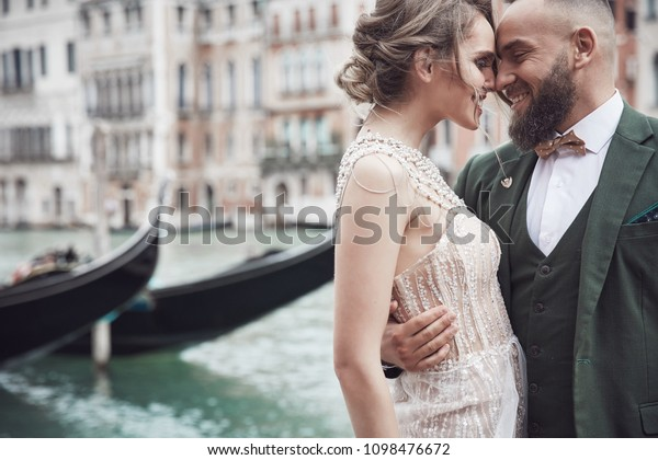 Happy wedding couple near the canal in Venice. Elegant woman in luxury ivory dress, messy updo hair, man in green three-piece suit and bow tie