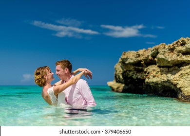 A happy wedding couple is standing in the blue ocean near the shore