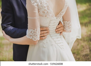 Happy wedding couple standing in park together. Close up of grooms hands on waist of beautiful bride. Color horizontal photo