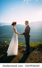 Happy wedding couple staying and watching each over with the beautiful landscape with mountains