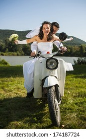 Happy wedding couple take a ride in a white motorcycle.