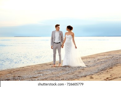 Happy wedding couple walking on beach