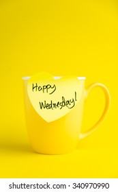 Happy Wednesday message on yellow mug.