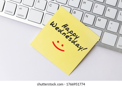 Happy Wednesday text on yellow paper note stick on computer keyboard