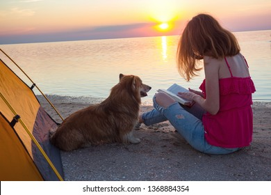 happy weekend by the sea - girl with a dog reading a book in a tent on the beach at dawn. Ukrainian landscape at the Sea of Azov, Ukraine
