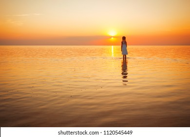 happy weekend by the sea - little girl looks at the sunset at the sea. Ukrainian landscape at the Sea of Azov, Ukraine