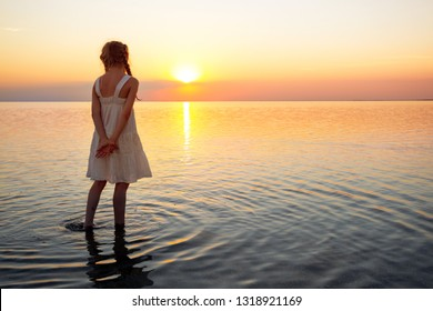 happy weekend by the sea - little girl walking at the sea at the sunset. Ukrainian landscape at the Sea of Azov, Ukraine